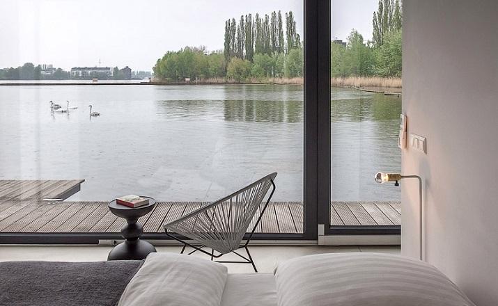 """""""Modernes Hausboot am Fluss. Die Inneneinrichtung ist schlicht, bodentiefe Fenster lassen weit blicken: Hier ist die Umgebung, die Stadt der Star.""""  Modernes Hausboot am Fluss Modernes Hausboot am Fluss 05"""